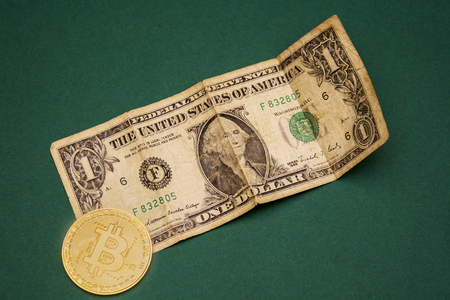 old one dollar paper money and bitcoin on green background