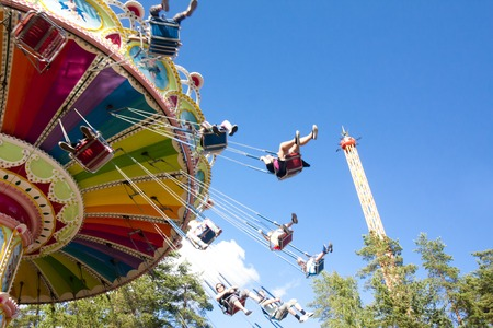 Foto de Colorful chain swing carousel in motion at amusement park on blue sky background - Imagen libre de derechos