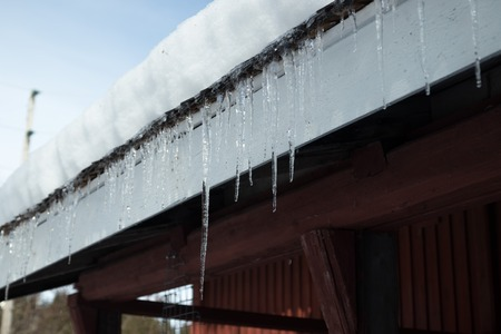 Sharp icicles and melted snow hanging from eaves of roof. Beautiful transparent icicles slowly gliding of a roof.