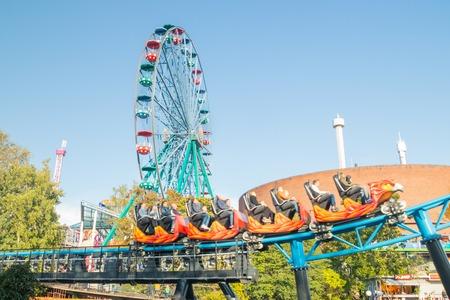 Photo for Helsinki, Finland - 14 September 2019: Linnanmaki Amusement Park, Rinkeli ferris wheel and new roller coaster Taiga in motion - Royalty Free Image