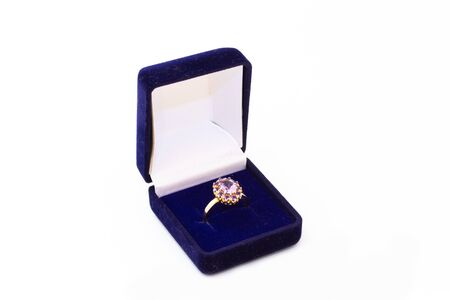 Photo pour Golden ring with purple gemstone in a blue jewelry box on white background - image libre de droit