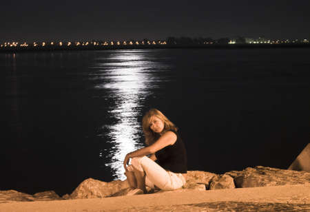 Blond woman sitting near river at the night