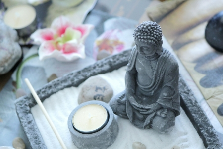 Grey stone buddha in front of a small yellow candle on a zen table