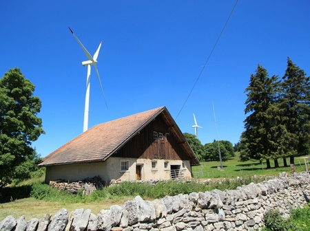Small house made of wood and white wind turbines in the country by beautiful weather