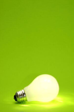 A lit light bulb on green.