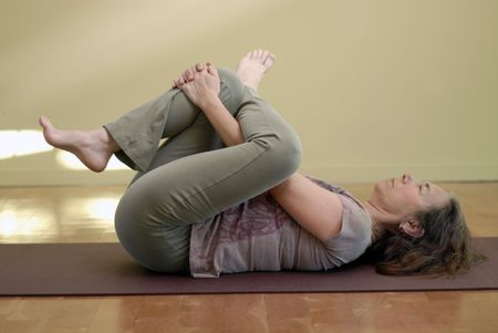 Middle aged female in a yoga pose.