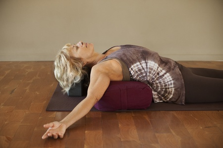 Foto für Middle age woman resting on a yoga bolster.  - Lizenzfreies Bild
