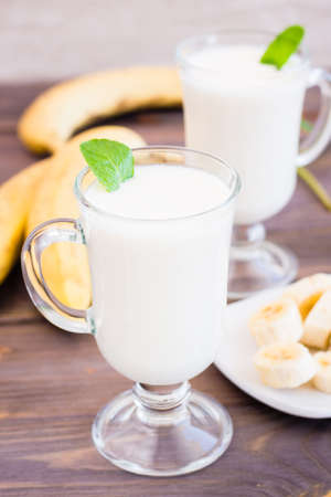 Photo for Banana smoothie with mint leaves in glasses on a wooden table - Royalty Free Image