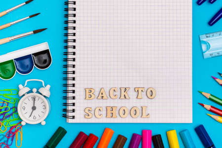 Photo for Back to school. Stationery, alarm clock and inscription in wooden letters in a notebook on a blue background. Top view. Copy space - Royalty Free Image