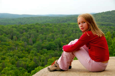 Young girl sitting on an edge of a cliff