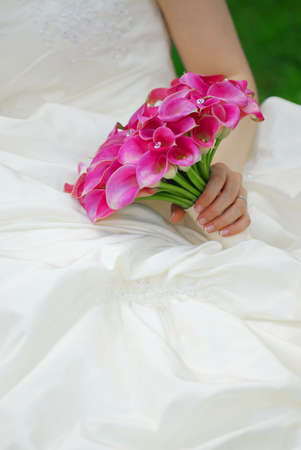 Bride in a wedding dress holding a bouquet of pink flowers