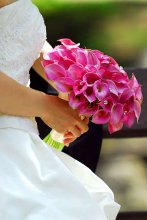 Bride in wedding gown holding bouquet of pink flowers