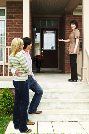 Real estate agent with couple welcoming to new home
