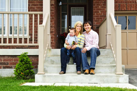 Young family sitting on front steps of house