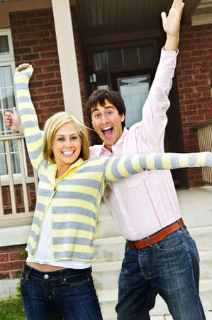 Young excited couple celebrating in front of home