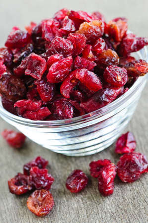Dried cranberries spilling out of glass bowl