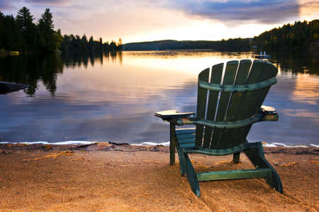 Wooden chair on beach of relaxing lake at sunset