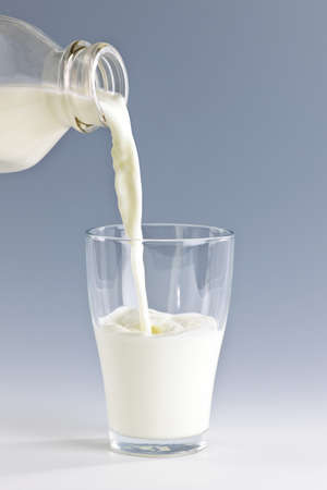 Pouring fresh white milk from bottle into a glass