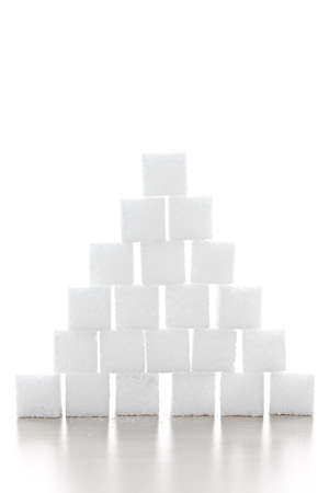 Pyramid of white sugar cubes stacked up on white background