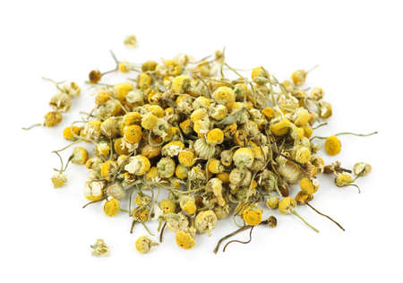 Pile of medicinal yellow chamomile herb buds on white background