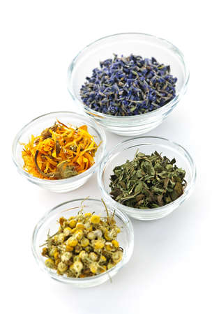 Bowls of dry medicinal herbs on white background