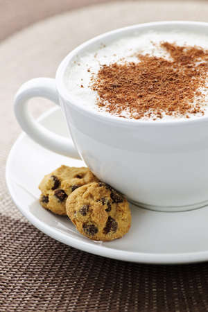 Photo pour Cappuccino or latte coffee in cup with frothed milk and cookies - image libre de droit