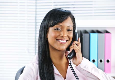 Portrait of smiling black business woman on phone in office