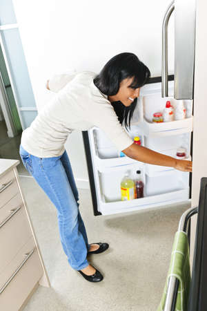 Black woman looking in fridge of modern kitchen interior