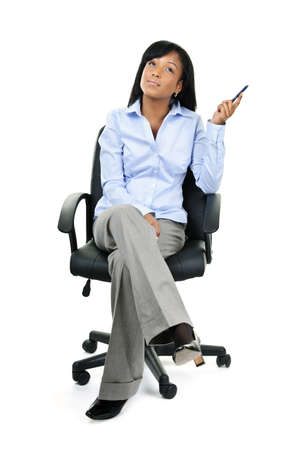 Young black businesswoman sitting and thinking in leather office chair