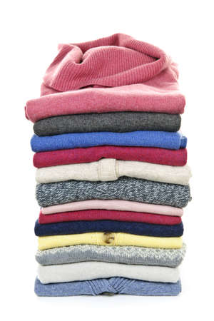 Stack of warm sweaters isolated on white background