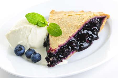 Slice of blueberry pie with vanilla ice cream and berries
