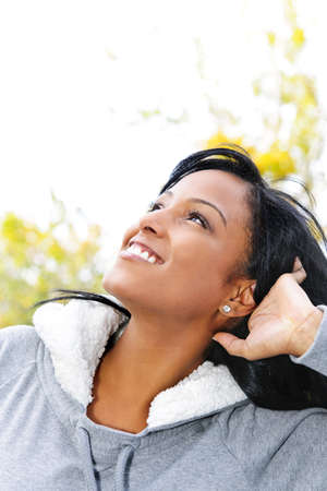 Photo pour Portrait of happy young black woman looking up outdoors in fall - image libre de droit