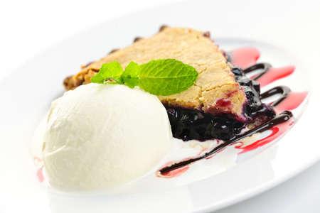 Slice of blueberry pie and vanilla ice cream served with dessert sauces