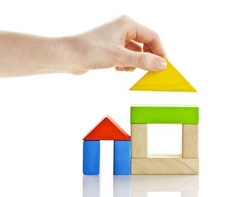Photo pour Wooden block houses under construction isolated on white background - image libre de droit