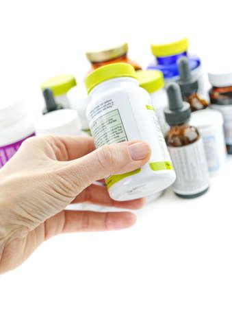 Hand holding medicine bottle to read label