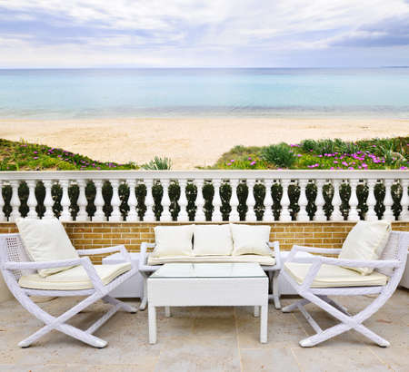 Patio with white wicker furniture with view of Mediterranean beach in Greece