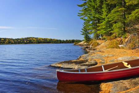 Red canoe on rocky shore of Lake of Two Rivers, Ontario, Canada