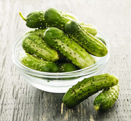 Fresh green pickling cucumbers in a glass bowl