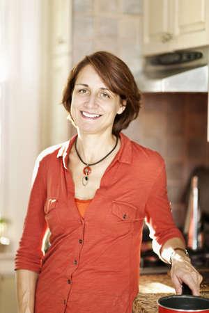 Foto für Smiling mature woman enjoying cooking in kitchen at home - Lizenzfreies Bild