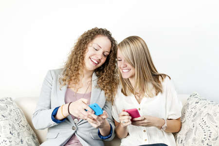 Two smiling women using mobile devices with colorful cases