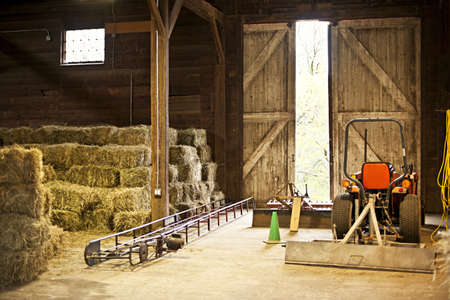 Interior of wooden barn with hay bales stacks and farm equipment