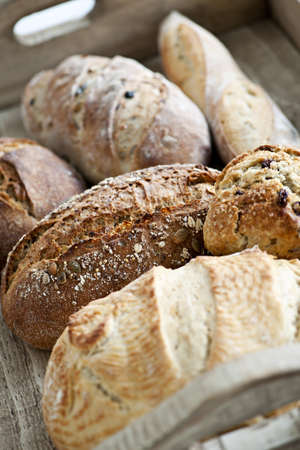 Photo pour Various kinds of fresh baked bread loaves in wooden tray - image libre de droit