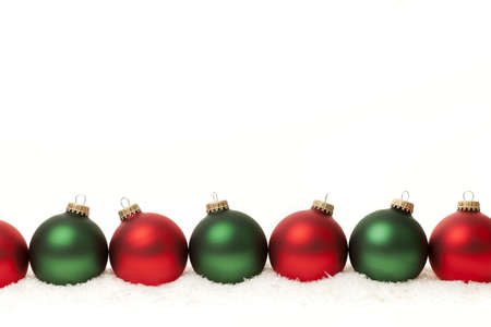 Row of green and red Christmas ornaments on white background
