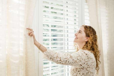 Foto de Happy woman looking out big bright window with curtains and blinds - Imagen libre de derechos