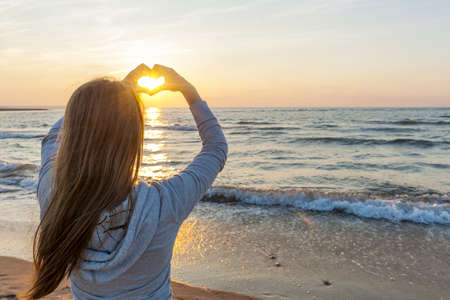 Blonde young girl holding hands in heart shape framing setting sun at sunset on ocean beach