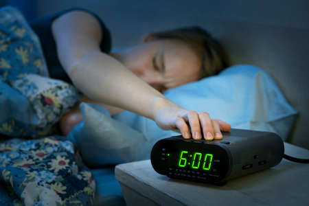 Photo pour Young woman pressing snooze button on early morning digital alarm clock radio - image libre de droit