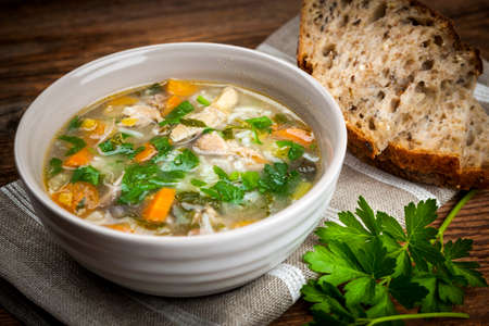 Chicken rice soup with vegetables in bowl and bread on rustic table