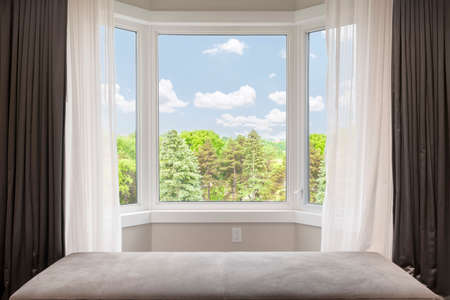 Photo pour Bay window with drapes, curtains and view of trees under summer sky - image libre de droit
