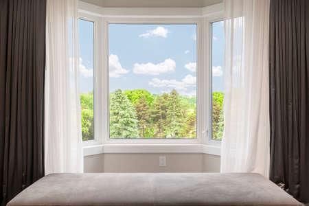 Foto de Bay window with drapes, curtains and view of trees under summer sky - Imagen libre de derechos