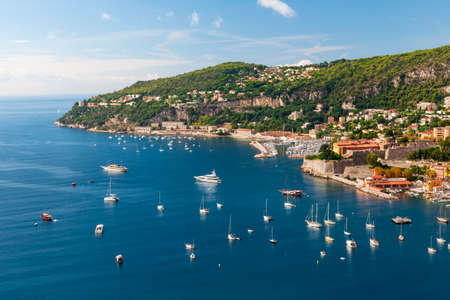 Coastal aerial view of Cap de Nice and medieval town VillefranchesurMer on scenic French Riviera with leisure boats anchored in Mediterranean sea harbor